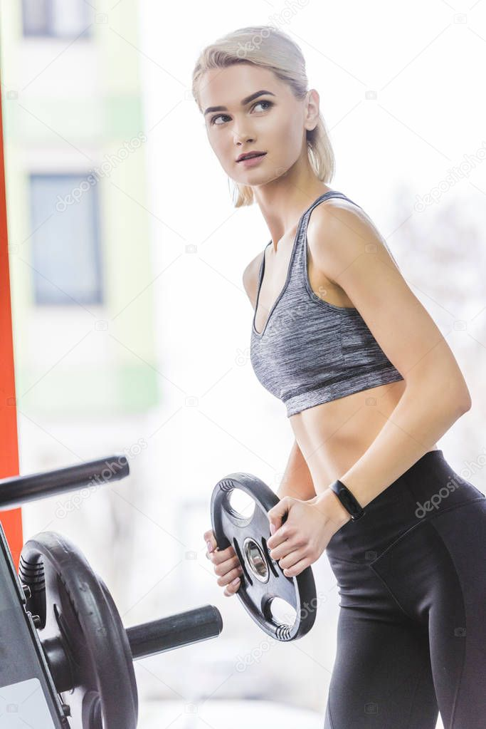 sportive young woman adding weight plate to gym machine