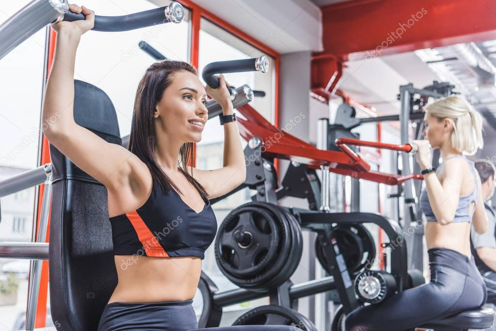 beautiful sportive women working out with gym machines
