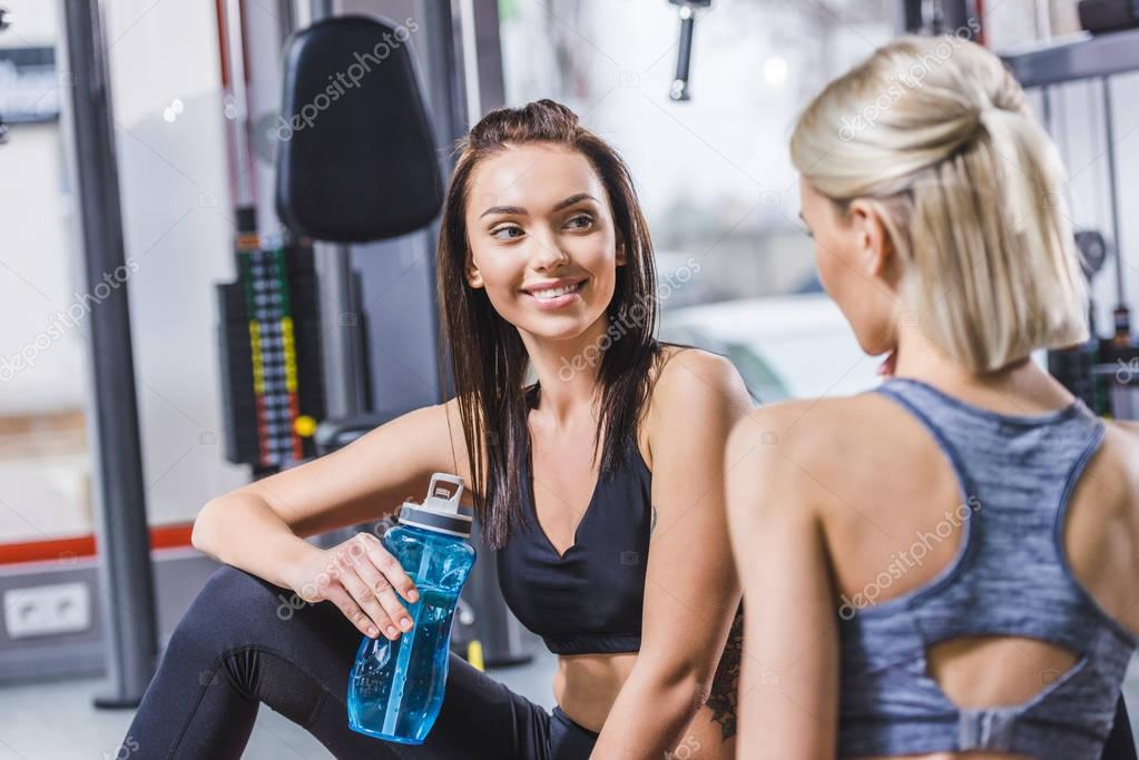 young sportive women relaxing after training at gym