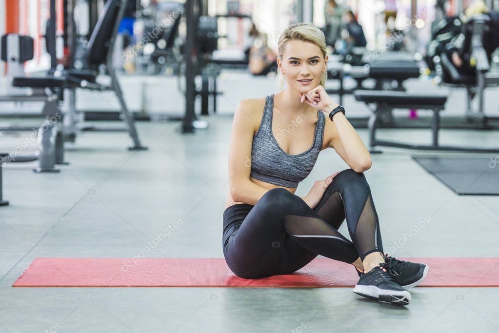 sportive young woman sitting on yoga mat at gym