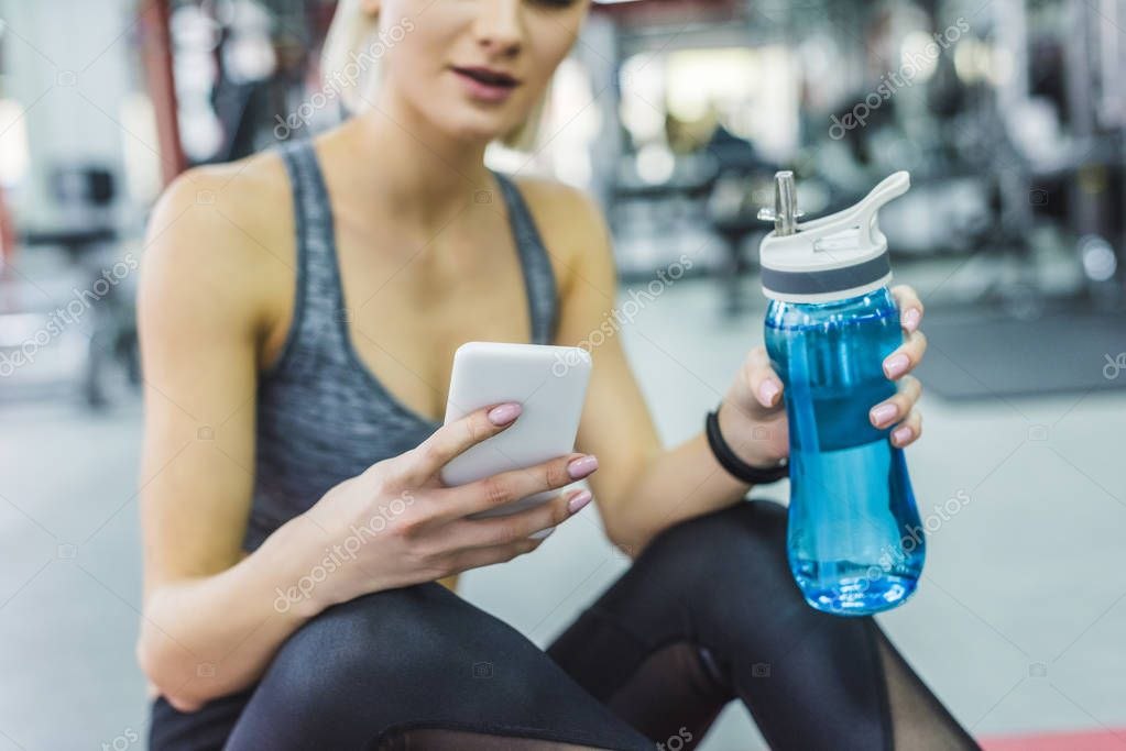 cropped shot of woman using smartphone at gym