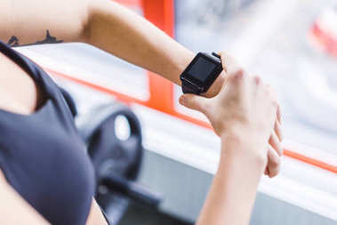cropped shot of woman checking fitness results on smart watch