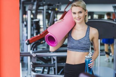 attractive young woman with rolled yoga mat and water bottle at gym