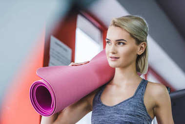 beautiful young woman with rolled yoga mat at gym