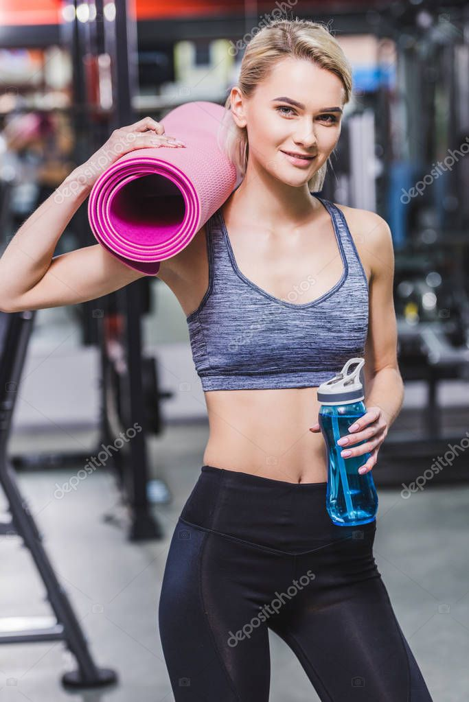 young woman with rolled yoga mat and water bottle at gym