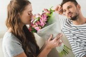 young woman with beautiful bouquet presented by boyfriend