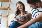 glückliches junges Paar Petting Katze zu Hause sitzend auf Etage
