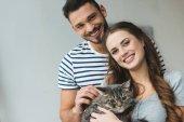mosolygó fiatal pár macska tartja a kezében, és keresi a kamera