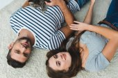 top view of young couple lying on floor with cute tabby cat
