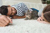 Fotografie happy young couple lying on floor with tabby cat