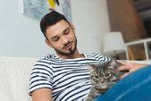 Fotografie pohledný mladý muž mazlení roztomilý mourovatá kočka, zatímco sedí na gauči