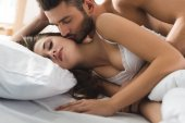 Photo young man embracing and kissing his girlfriend from behind in bed