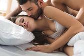 mladý muž objímá a líbá svou přítelkyni zezadu v posteli