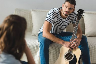 young man sitting on couch with guitar and looking at girlfriend at home