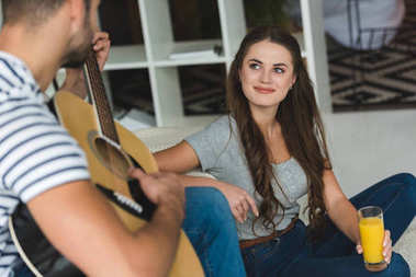 man playing guitar for girlfriend while she sitting on floor with juice