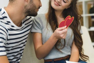 woman showing valentines day greeting card to boyfriend