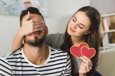 young woman covering eyes of boyfriend with hand and holding valentines day greeting card