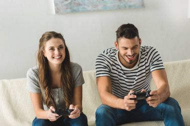 smiling young couple playing games with gamepads at home