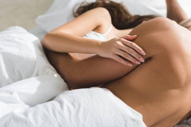 cropped shot of couple embracing in bed in morning