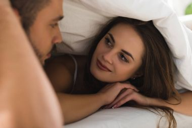 young couple under blanket looking at each other in bed