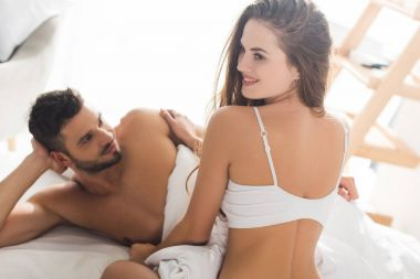 smiling young couple in underwear spending time in bed in morning