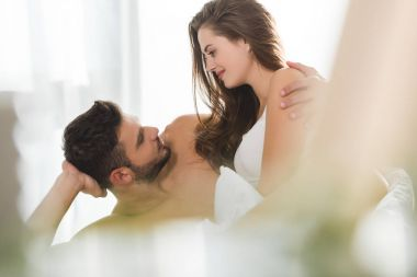 attractive young couple embracing in bed at sunny morning