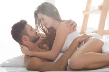 smiling young couple in underwear embracing in bed at sunny morning