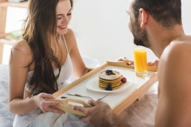 man giving breakfast in bed for beautiful happy girlfriend