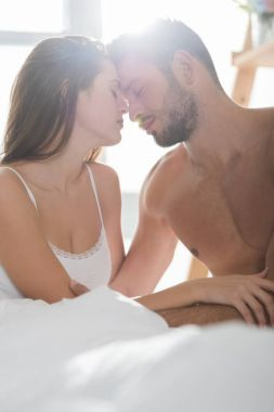 beautiful young couple in underwear cuddling in bed in morning