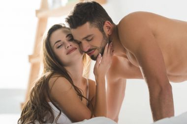 happy young couple in underwear cuddling in bed in morning