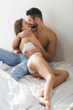 happy young couple embracing and kissing in bed in morning