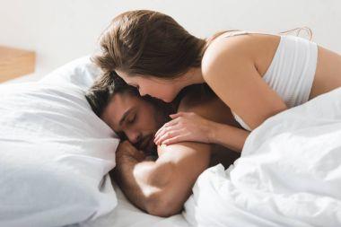 beautiful young woman lying on her sleeping boyfriend in morning