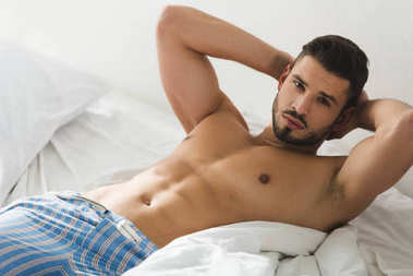 shirtless young man in pajamas pants lying in bed