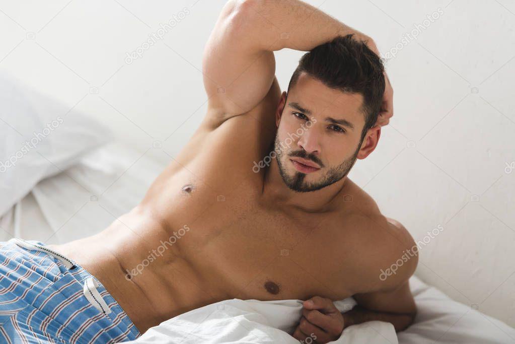 shirtless young man in pajamas pants lying in bed and looking at camera
