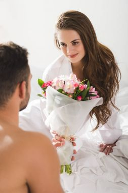 man presenting beautiful bouquet to girlfriend in morning in bed