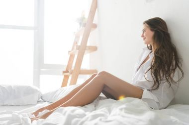 beautiful young woman relaxing in bed in morning