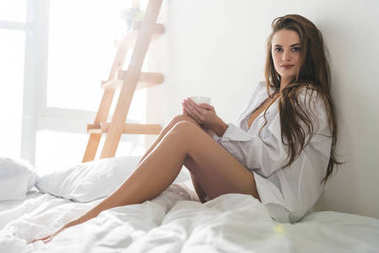 attractive young woman with cup of hot drink in bed
