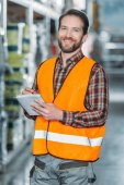 Fotografie usměvavý dělník v bezpečnostní vesta psaní v programu Poznámkový blok ve skladu