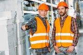 zwei männliche Arbeiter halten Walkie Talkie in Lagerhalle