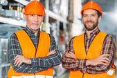 Fotografie zwei männliche Arbeiter in Warnwesten und Helmen mit verschränkten Armen in Lagerhalle