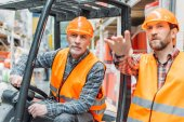 Arbeiter und sein älterer Kollege arbeiten mit Gabelstapler-Maschine im Lager