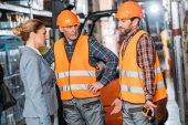 Männliche Arbeiter in Warnwesten und Helmen im Gespräch mit dem Inspektor in der Lagerhalle