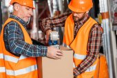 male workers in safety vests and helmets packing cardboard box with scotch tape