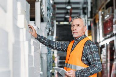 Senior worker using digital tablet in storehouse stock vector