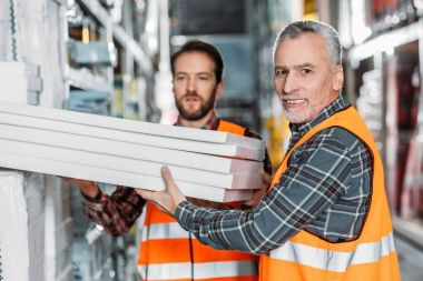 two male workers holding styrofoam in shipping stock