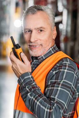 Senior worker using walkie talkie in storage stock vector