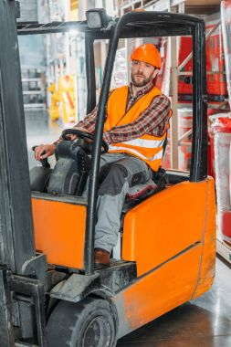 Male worker in safety vest and helmet sitting in forklift machine in storage stock vector
