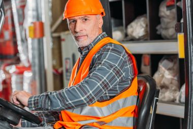 Senior worker in safety vest and helmet sitting in forklift machine in storage stock vector