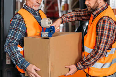 cropped view of male workers in helmets packing cardboard box with scotch tape