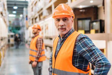 Senior worker in safety vest and helmet, coworker standing behind in storage stock vector